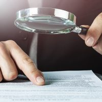 Business analytics and statistics. Businessman with report using a magnifying glass.